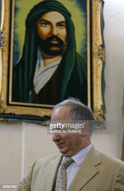 Iraqi Governing Council member Ahmed Chalabi makes his way past a portrait of Imam Ali the cousin of Islam's Prophet Mohammed during a visit to the...