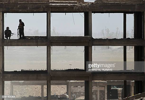 TOPSHOT Iraqi government forces and elite counterterrorism service patrol from the edge of Shuhada neighbourhood southern Fallujah during an...