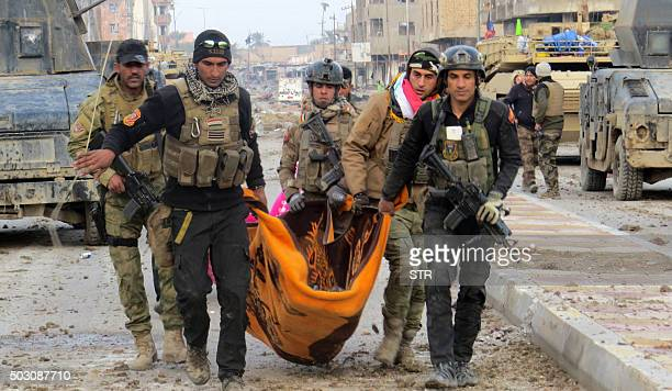 Iraqi government forces and members of Iraq's elite counterterrorism service carry the body of a comrade during battles with Islamic State group...