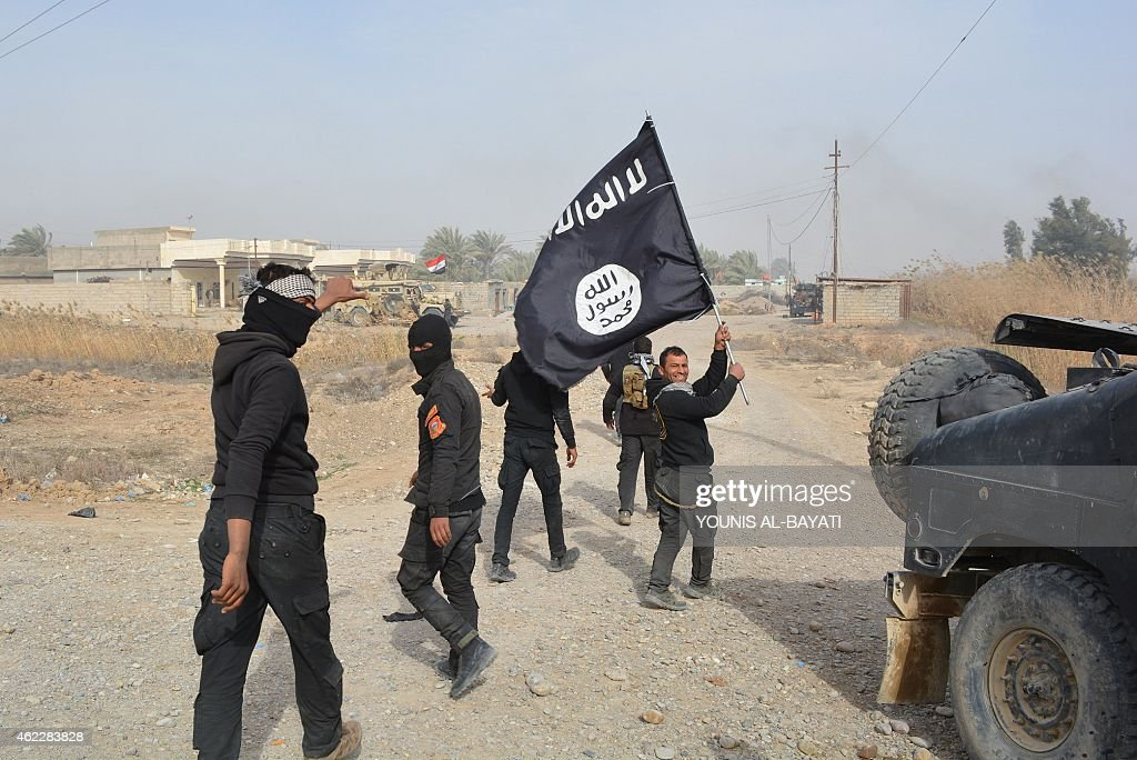Iraqi government forces celebrate while holding an Islamis Sate (IS) group flag after they claimed they have gained complete control of the Diyala province, northeast of Baghdad, on January 26, 2015 near the town of Muqdadiyah. Iraqi forces have 'liberated' Diyala province from the Islamic State jihadist group, retaking all populated areas of the eastern region, a top army officer said today. The symbolic victory for Baghdad, which has at times struggled to push IS back, could clear the way for further advances against the jihadists .