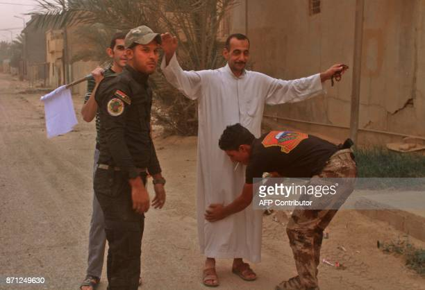 Iraqi government forces check civilians after they came out into the street in alQaim on November 6 after Islamic State group jihadists were ousted...