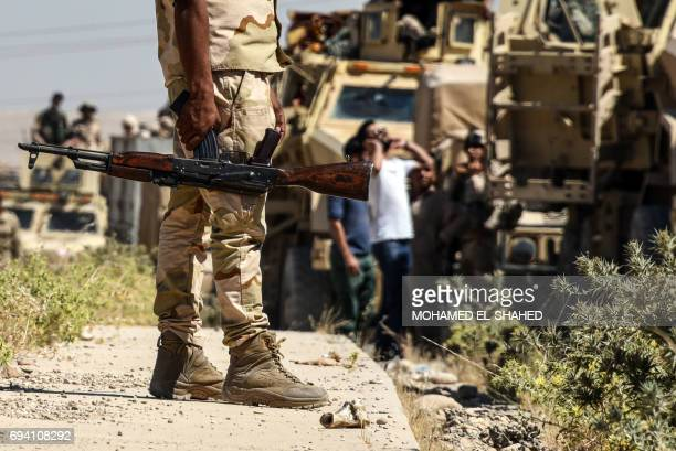 TOPSHOT Iraqi government forces drive down a road leading to Tal Afar on June 9 during ongoing battles to retake the city from Islamic State group...