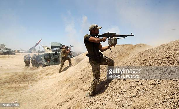 TOPSHOT Iraqi government forces fire their weapons near alSejar village northeast of Fallujah on May 26 as they take part in a major assault to...
