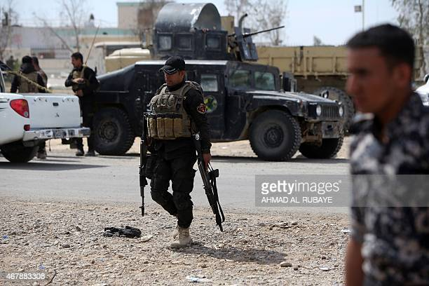 Iraqi government forces gather next to their vehicles on the western outskirts of Tikrit on March 28 during a military operation to retake the...