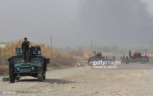 Iraqi government forces gather on a road after they claimed they have gained complete control of the Diyala province northeast of Baghdad on January...