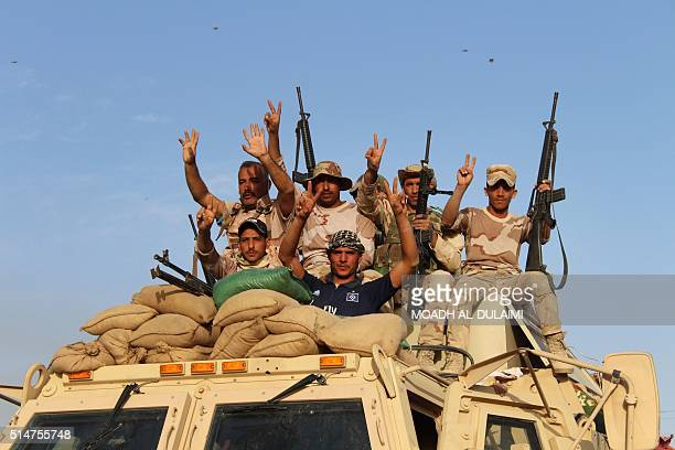Iraqi government forces gesture to the camera on March 10 2016 after retaking the town of Zankura northwest of Ramadi from the Islamic State jihadist...