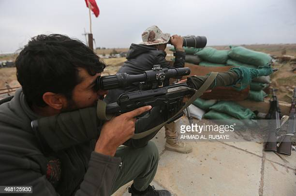 Iraqi government forces keep watch from a position on the southern outskirts of Tikrit on March 30 during a military operation to retake the city...