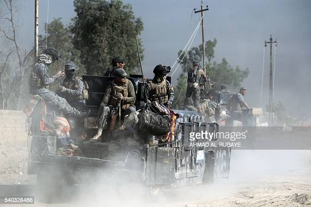 Iraqi government forces sit in the back of their vehicle during an operation backed by air support from the USled coalition in Fallujah's southern...