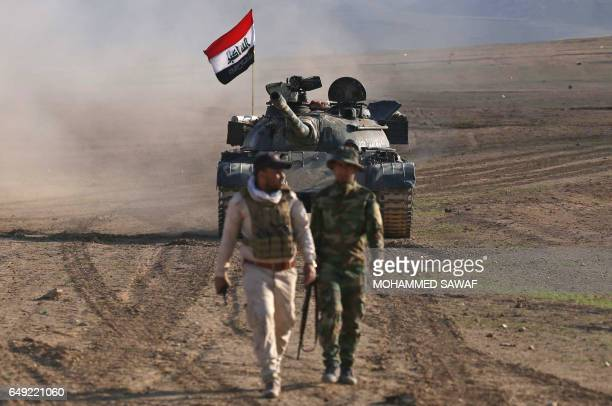 Iraqi government forces supported by fighters from the Abbas Brigade which fight under the umbrella of the Shiite popular mobilisation units advance...