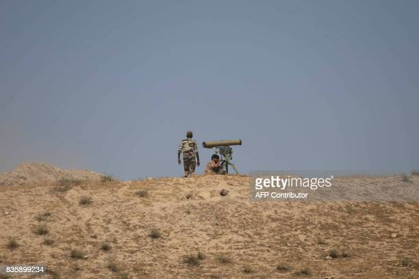 Iraqi government forces supported by fighters from the Abbas Brigade which fights under the umbrella of the Shiite popular mobilisation units hold a...