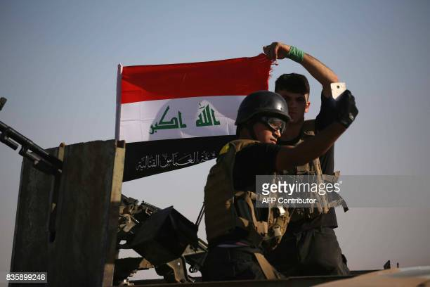 Iraqi government forces supported by fighters from the Abbas Brigade which fights under the umbrella of the Shiite popular mobilisation units hold...