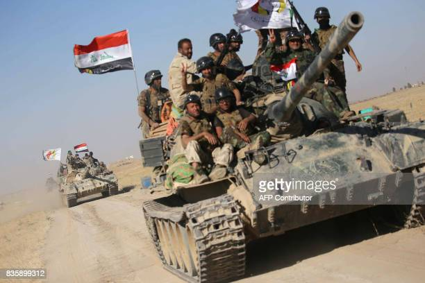 Iraqi government forces supported by fighters from the Abbas Brigade which fights under the umbrella of the Shiite popular mobilisation units advance...