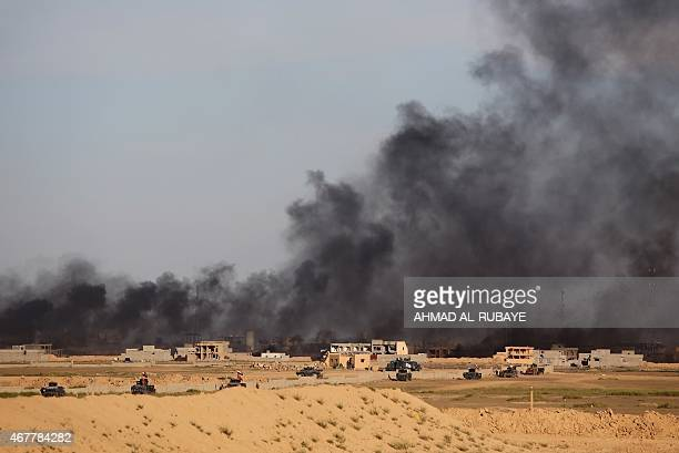 Iraqi government forces vehicles are positioned on the western outskirts of Tikrit on March 27 as smoke rises during a military operation to retake...