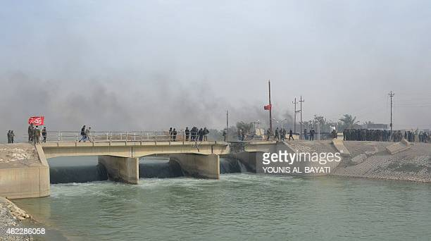 Iraqi government forces walk over a bridge after they claimed they have gained complete control of the Diyala province northeast of Baghdad on...