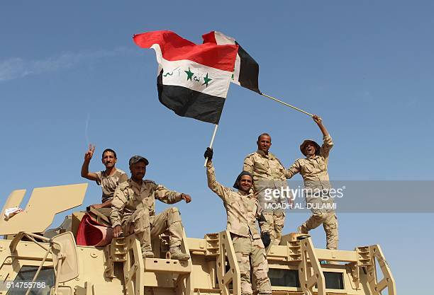 Iraqi government forces wave their national flags on March 10 2016 after retaking the town of Zankura northwest of Ramadi from the Islamic State...