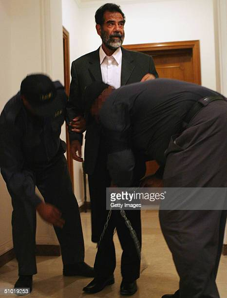 MILITARY*** Iraqi guards unshackle former Iraqi President Saddam Hussein before he is lead into an Iraqi courtroom July 1 2004 in Baghdad Iraq to...