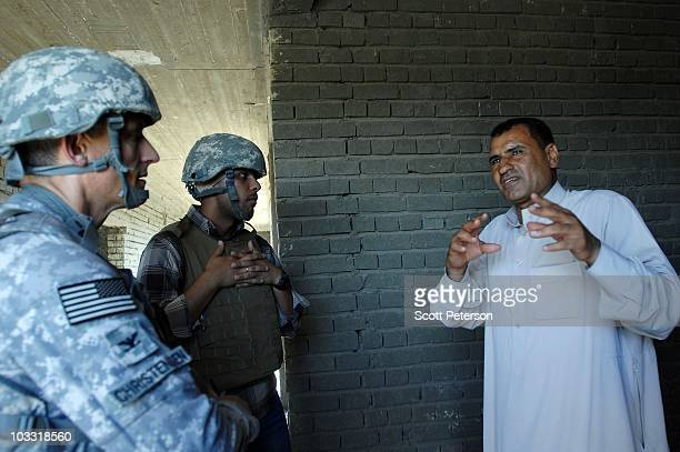 Iraqi headmaster Bassim speaks to US Army Col Jon Christensen as he inspects the USfunded AlNamiya School where the project was stopped by the US...