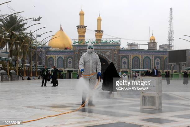 Iraqi health workers disinfect the area around the Imam Hussein Shrine in the central Iraqi holy shrine city of Karbala on March 15, 2020 amidst...