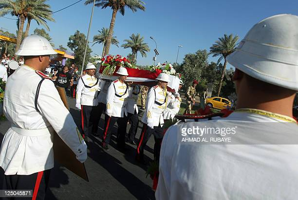 Iraqi honour guard carry the coffin of sculptor Mohammed Ghani Hikmat whose art abounds in public squares across Baghdad after his body arrived from...