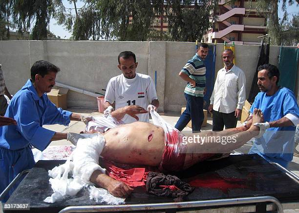 Iraqi hospital workers move the body of one of the victims of a suicide bombing on October 8 2008 outside a hospital of the restive Iraqi city of...