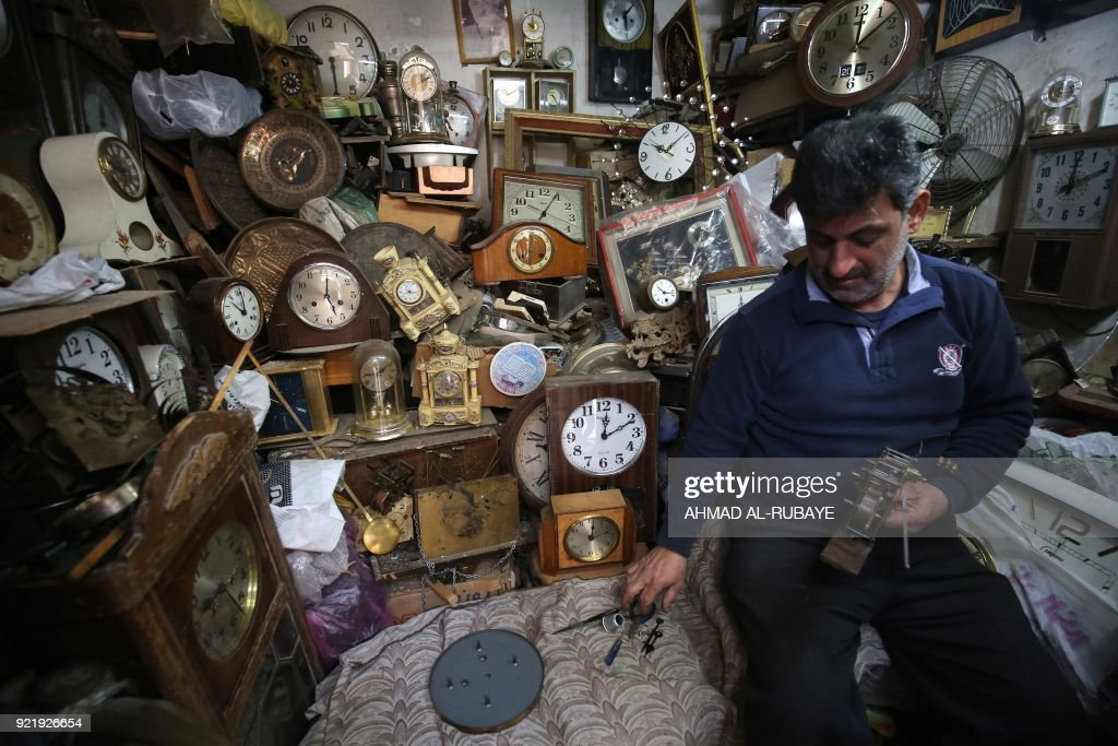 Iraqi Hussein Mahmud, 45, works on repairing old and antique clocks at his warehouse in Baghdad's Maidan area on February 20, 2018. Mahmud started this job 30 years ago and says he was taught by his father. He collects clocks from auctions and street sellers, some of these date from 60 to 150 years, and especially German and American ones, after repairing, he sells these clocks to antique fans. /