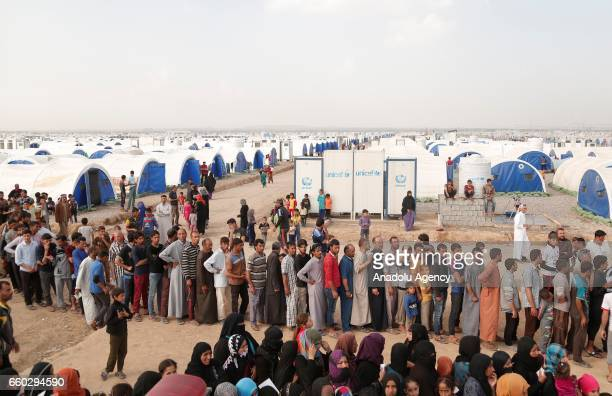 Iraqi internally displaced people, fled from clashes between Iraqi Army and Daesh terrorists, wait in a line to get humanitarian aid at Jadah refugee...