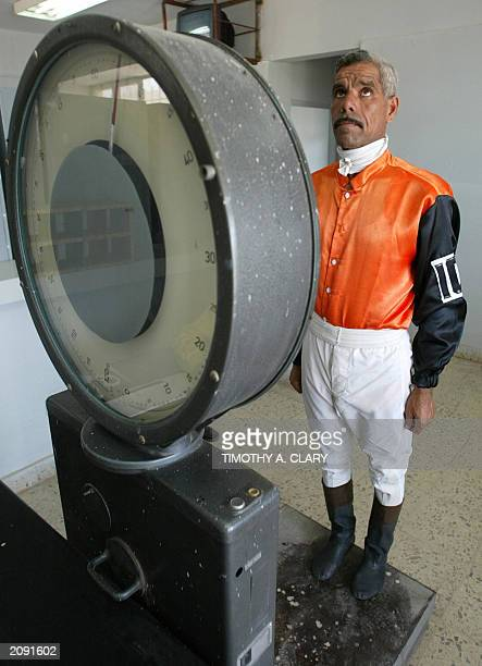 Iraqi jockey Bakri Abdel Hameed stands on the scale as he weights in before the start of the first race at the Equestrian Club in Baghdad 11 June...