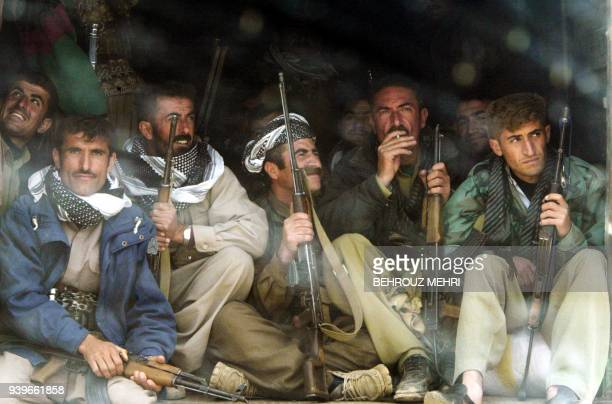 Iraqi Kurd Peshmerga fighters of Patriotic Union of Kurdistan sit in the pick-up of a military truck on their way to Halabja in the far southeast...