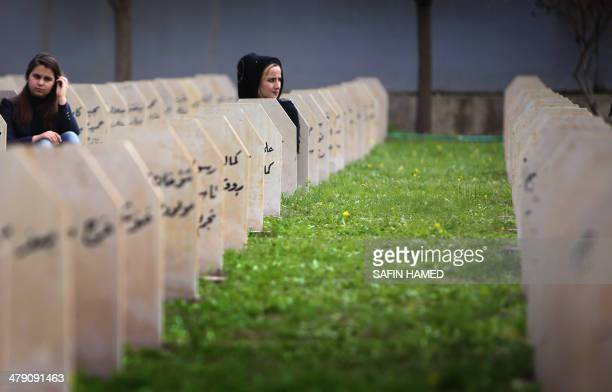 Iraqi Kurd women sit among the headstones as they visit a grave yard for the victims of a gas attack by former Iraqi president Saddam Hussein in 1988...