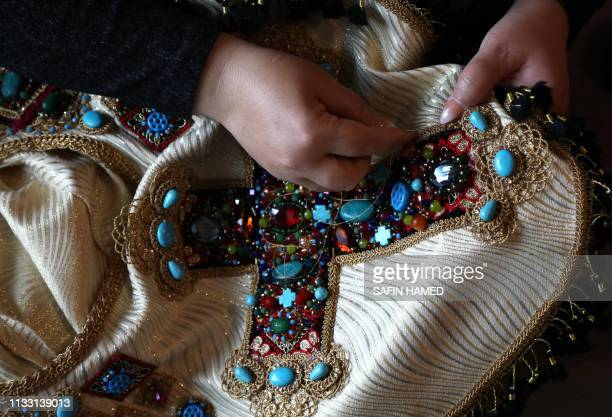 Iraqi Kurdish artist Shanaz Jamal embroiders a robe ornated with a big cross one of the religious symbols of communities living in Iraq's multiethnic...