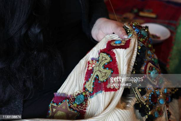 Iraqi Kurdish artist Shanaz Jamal embroiders a robe ornated with religious symbols of communities of Iraq's multiethnic north in Arbil the capital of...