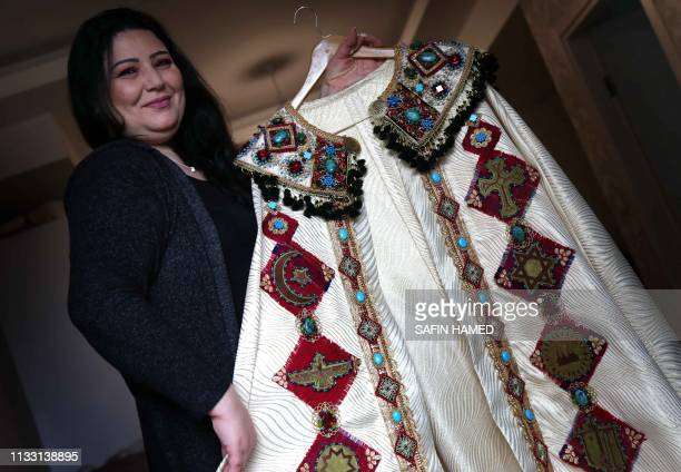 Iraqi Kurdish artist Shanaz Jamal poses with one of her embroidered robes ornated with religious symbols of communities of Iraq's multiethnic north...