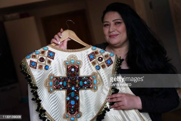 Iraqi Kurdish artist Shanaz Jamal shows an embroidered robe ornated with a big cross one of the religious symbols of communities living in Iraq's...