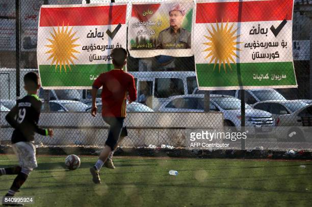 Iraqi Kurdish boys play football past posters bearing the image of Iraqi Kurdish leader Massud Barzani and supporting independence in the upcoming...