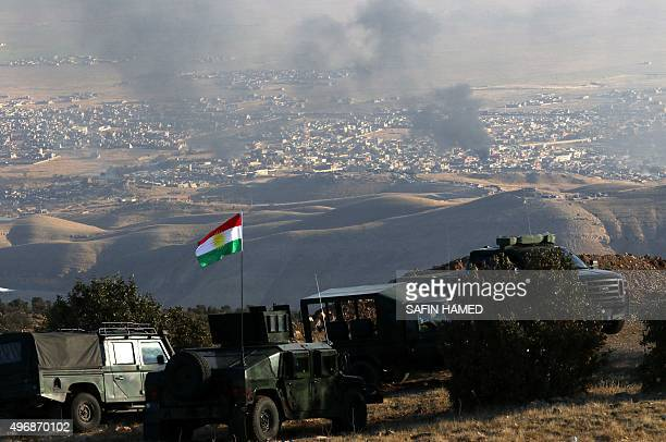 Iraqi Kurdish forces are seen stationed on a hill top near the northern Iraqi town of Sinjar as smoke billows during an operation by Iraqi Kurdish...