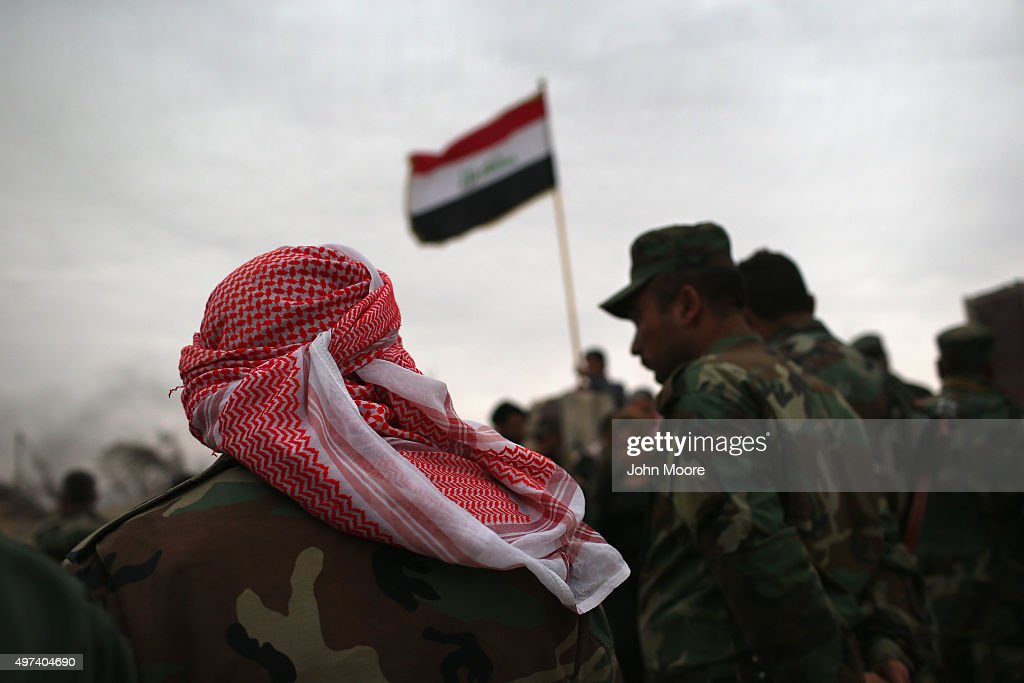 Iraqi Kurdish forces attend a flag-raising ceremony at a post office destroyed by an airstrike on November 16, 2015 in Sinjar, Iraq. Kurdish forces, with the aid of months of U.S.-led coalition airstrikes, liberated the town from ISIL extremists, known in Arabic as Daesh, in recent days. Although the battle was deemed a major victory, much of the city lay in complete ruins.