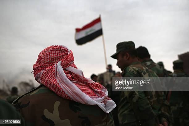 Iraqi Kurdish forces attend a flagraising ceremony at a post office destroyed by an airstrike on November 16 2015 in Sinjar Iraq Kurdish forces with...