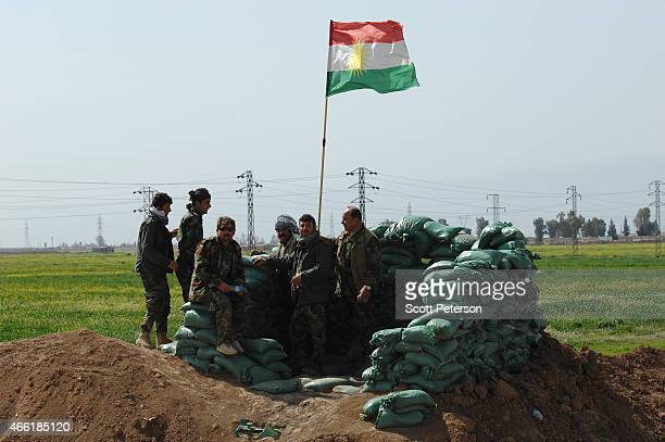 Iraqi Kurdish forces stand in sandbagged post as they push the frontline forward against ISIS forces in the Tal alWard district 20 miles southwest of...