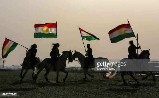 TOPSHOT Iraqi Kurdish horsemen ride carrying Kurdish flags celebrating their flag day in the northern city of Arbil the capital of the autonomous...