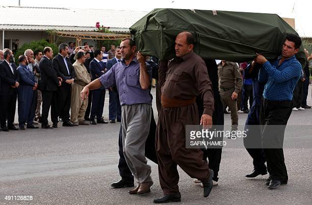Iraqi Kurdish men carry the coffin of a Kurdish migrant who died strangled in a lorry in Austria alongside other migrants during a repatriation...