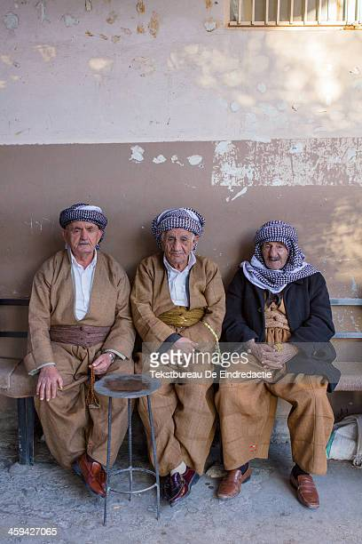 CONTENT] Iraqi Kurdish men wearing traditional baggy trousers and headscarves passing time in the late afternoon sun having tea and playing with...