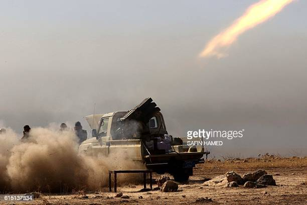 Iraqi Kurdish Peshmerga fighters fire a multiple rocket launcher from the top of Mount Zardak about 25 kilometres east of Mosul as they take part in...
