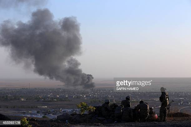 Iraqi Kurdish Peshmerga fighters look on as smoke billows from the town Makhmur about 280 kilometres north of the capital Baghdad during clashes with...