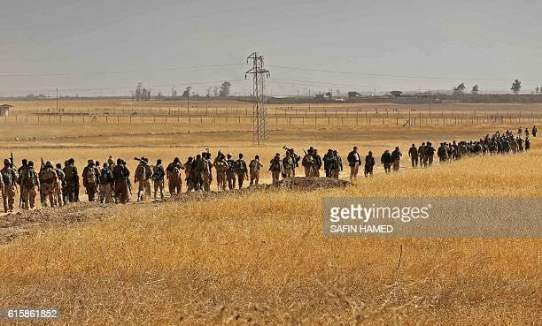 TOPSHOT Iraqi Kurdish Peshmerga fighters march down a dirt road in Nawran village some 10km north east of Mosul on October 20 during the ongoing...