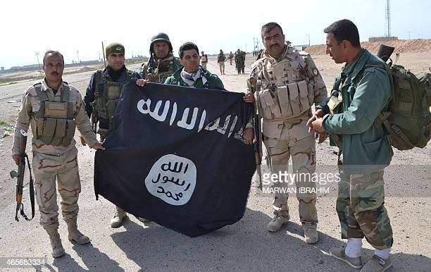 Iraqi Kurdish Peshmerga fighters pose for a photo holding an Islamic State group flag in the village of Sultan Mari west of the city of Kirkuk on...