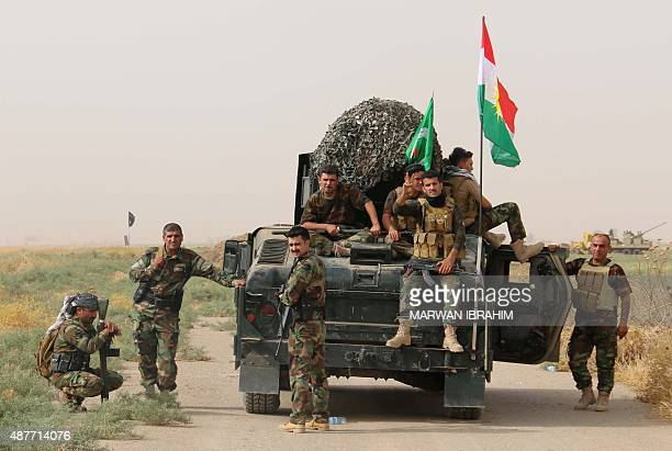 Iraqi Kurdish Peshmerga fighters pose for a photo next to a military vehicle bearing the Kurdish flag after they reportedly captured several villages...