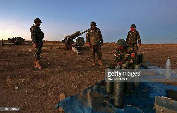 TOPSHOT Iraqi Kurdish Peshmerga fighters prepare their weapons as they gather on the top of Mount Zardak about 25 kilometres east of Mosul on early...