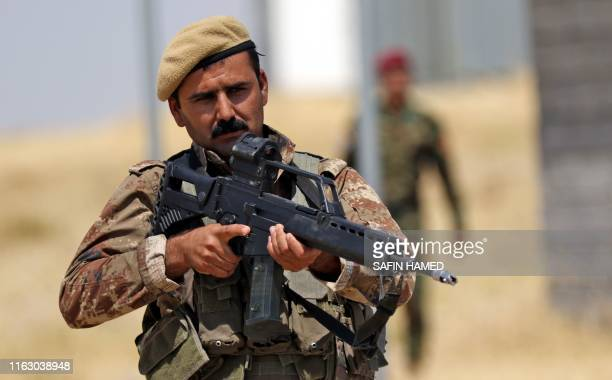 Iraqi Kurdish Peshmerga forces using German-made assault rifles attend a training session by German military officers during the German Defence...