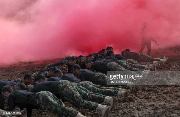 Iraqi Kurdish Peshmerga officers perform drills as they take part in a graduation ceremony in the Kurdish town of Soran, about 100 kilometres...