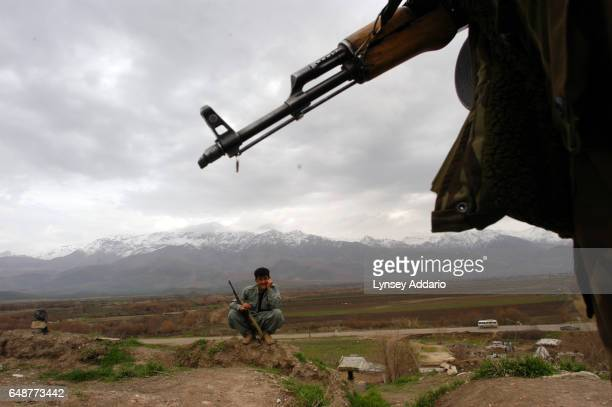 Iraqi Kurdish Peshmerga stand guard near the main road to Halabja in Northern Iraq February 5 2004 As Iraq works towards creating uniform security...